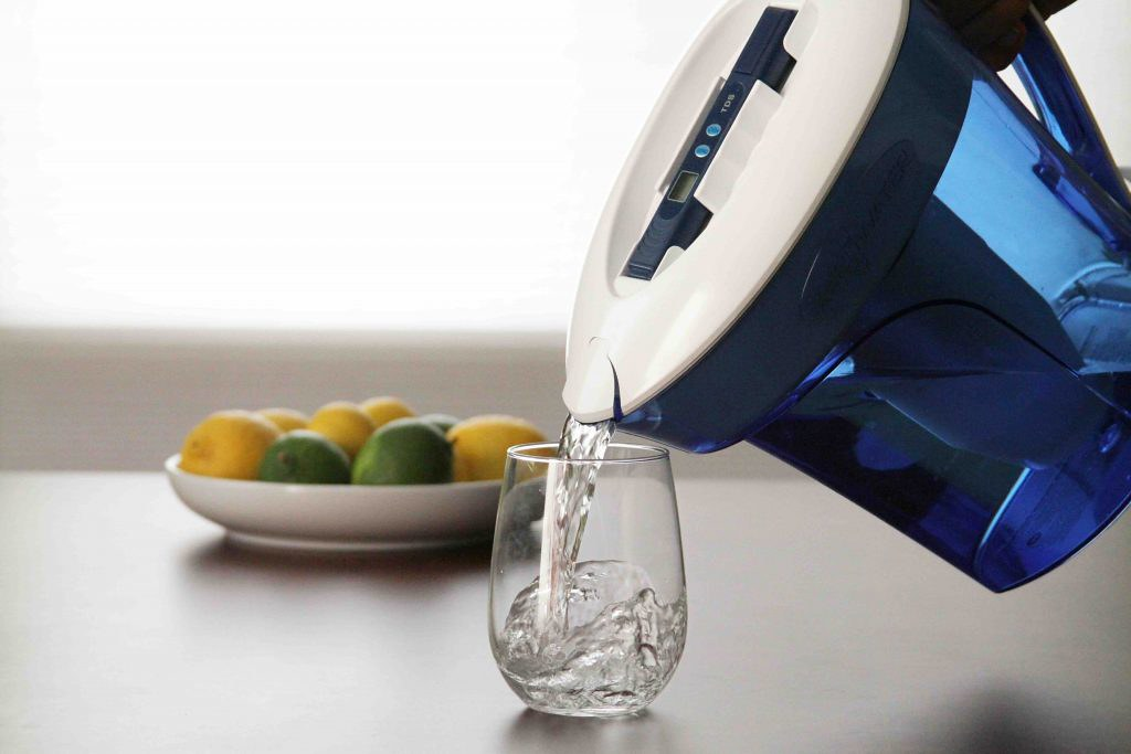 pouring water from water filter pitcher into glass